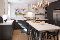 A contemporary bistro-style kitchen with bi-color cabinetry, marble surfaces and black Thonet bentwood chairs - Canadian House & Home