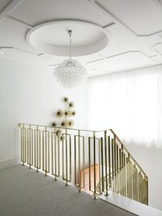 This brass stair railing is a piece of art unto itself.  Compliments the C. Jere sculpture on the wall and the white and grey color palate.