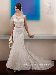 An all-over lace fit and flare bridal gown with bateau neckline, satin belt at natural waistline with beading ornament at center front and a bow tie in the back with buttons and a chapel train.