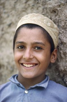 A smiling boy leans against a wall at his school, in a camp for Afghan refugees, in Pakistan's north-western city of Peshawar, in 1988. © UNICEF/NYHQ1988-0338/Isaac