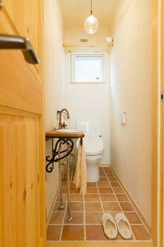 木×塗り壁×テラコッタにアンティーク調の手洗器を合わせたおしゃれなトイレ