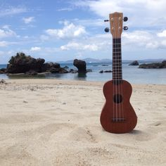 My ukulele on the beach under the blue sky and white clouds. Summer in Okinawa, Japan.