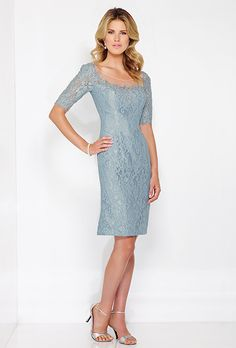 Lace knee-length sheath with illusion three-quarter length sleeves. Illusion wide scooped neckline, illusion back with covered buttons and center back slit.
