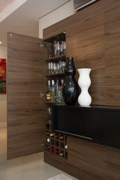 """Neste apartamento em Porto Alegre (RS), a adega foi inserida no painel para TV. """"A idéia era de ter um móvel limpo, sem espaço para objetos expostos porém que tivesse um aproveitamento interno"""", conta a arquiteta Aline Dal´Pizzol, que assina o espaço. O armário é em MDF e comporta até 20 garrafas."""