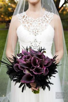 Dramatic deep purple bouquet of calla lilies and feathers.