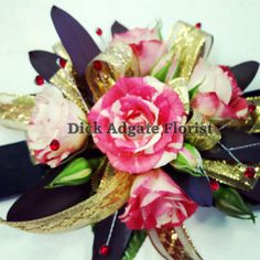 Cream and red sweetheart roses with safari sunset leaves. This is a simple and stunning corsage for homecoming or prom. The red spray gems add that little bit of bling. Dick Adgate Florist original.