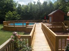 Stunning Above Ground Pools with Decks; Additional Ideas: Amazing Long Bridge Rounded Blue Above Ground Pools With Decks Of Wood Wooden Fence And Lust Green Trees With Handrail