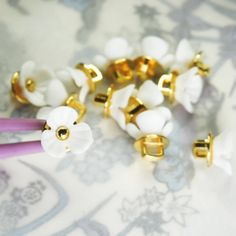 This is a lot of 12 Cute tiny flower buttons with shanks for sewing, for dainty jewelry making, and for creating embellishments and accessories.These buttons have very large and square 8 mm shanks.- 10 mm- White and gold colors.- Made from res... Button Flowers, Tiny Flowers, Fancy Buttons, Dainty Jewelry, Vintage Brooches, Embellishments, Pearl Earrings, Jewelry Making, Sewing