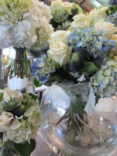 A touch of blue in bridal party flowers awaiting stems to be bound in satin ribbon.