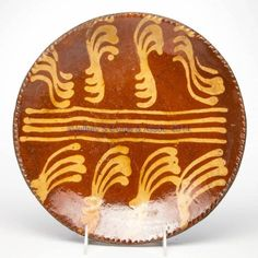 """Jeffrey Evans 11/15/14 Lot# 218.  Description:   AMERICAN SLIP-DECORATED EARTHENWARE / REDWARE PLATE, lead-glazed, shallow form with coggled rim, center with yellow-slipped decoration. 18th or 19th century. 1 3/4"""" H, 11 1/8"""" D.  Very good appearance, professional restoration to two hairlines, area of rim, and glaze. Provenance: From a New York City collection. Estimate: $100 - $200. Realized $288 with 15% premium."""