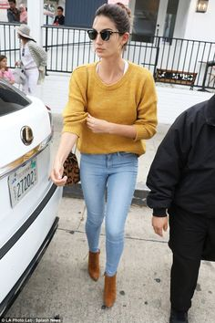 So stylish: Lily looked fabulous in a mustard yellow sweater and tight jeans as she headed...