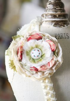 DIY/Go-figure: a colorful flower corsage pin features layers of hand cut textiles in pink, red and garden green -- full of pretty textures, fun mixed patterned fabrics, and a vintage glass button with the a sweet floral painted design.