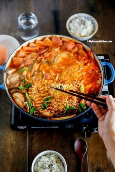 Budae jjigae What is it? A stew made with kimchi, ramen, slices sausages, spam, tofu, and rice cake.  Created after the Korean war to make economic use of American ingredients, this stew has EVERYTHING, including spam (which seems to find its way into a lot of Korean dishes.) Recipe here.