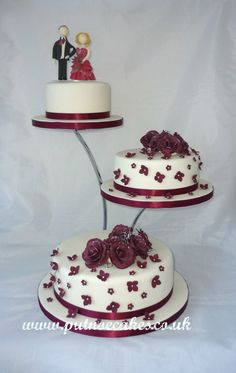 Ivory wedding cake with burgundy roses and blossoms, the topper is also hand made from Artista Soft