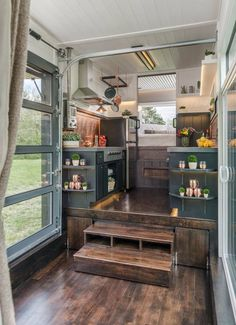 The kitchen sits on top of a raised platform and a nested dining set pulls out from under the platform to accommodate up to 12 people. The owners love to entertain!