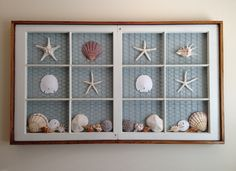 Made from two matching old window sashes backed with chicken wire then backed with painted bead board paneling.  Shell collection applied with hot glue gun...viola!  A sea shore wall hanging!