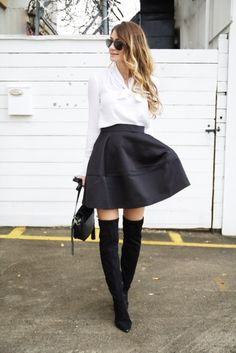 Girl wearing white blouse with bow, short black flair skirt, over the knee boots, holding purse #boots #skirt #holidaylook #ontheblog