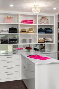 Luxurious walk-in closet is fitted with a crystal beaded semi flush mounted hung above a t-shaped white quartz countertop placed atop white drawers with polished nickel pulls and see through jewelry drawers placed in front of a mirrored backsplash fixed beneath white shelves.
