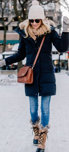 #spring #outfits woman wearing black bubble coat and blue jeans with brown crossbody bag. Pic by @kellyinthecity