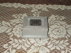This pretty pearly white grey box is topped with a silvery ornament