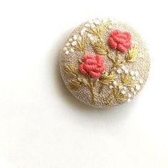 (こちらの作品は、他サイトでも販売中のため万が一注文が重なった場合は、同じ構図で新しく製作したものをお送りいたします。手刺繍ですので、全く同じにはならない場合もございますがあらかじめご了承ください。)バラの花をメインに、草花の刺繍をあしらった作品です。生地はシックで爽やかなグレー色の木綿を使用。ヘアゴムに仕上げました。上品な刺繍の大きめくるみボタンで、存在感があります。ゴム部分は、好きな色 太さのものにかえてご利用いただいても良いように、あえて簡素な作りにしてあります。ヘアゴムの作品ですが、追加料金で、ブローチ仕様への変更が可能です。詳しくは商品名*ヘアゴムをブローチ仕様へ変更いたします*をご覧ください。手刺繍のため、同じものは二つとありませんが、同じモチーフでのオーダーは可能です。くるみボタン直径約4cmくるみボタン/金属生地、刺繍糸/綿