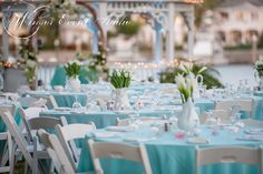 Reception dining tables draped with Tiffany blue linens and featuring white ceramic pitcher centerpieces with varying white flowers