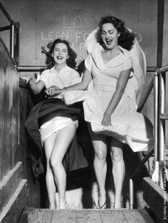 1953: Valerie Carton and Patricia Webb are surprised by a revealing gust of wind in the funhouse