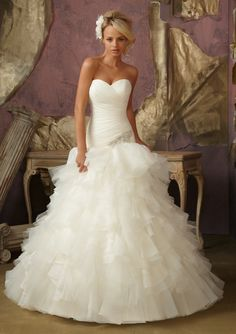 """#MoriLee Style 1856 - Diamante Applique on Ruffled Organza and Tulle.  Available in three lengths: 55"""", 58"""", 61"""". Colors Available: White/Silver, Ivory/Silver. Sizes Available: 2-28.  Folded and ruffled organza gift this modern ball gown a romantic ethereal feel.  The drop waist is subtle and has just a touch of sparkle with a diamante appliqué."""
