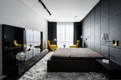 In this black and white bedroom, one wall is entirely covered in custom-designed black leather panels that act as a headboard. A pop of color has been introduced with bright yellow chairs, that have been used draw your eye to the window.