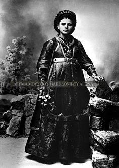 Ολόσωμη αναμνηστική φωτογραφία, η οποία απεικονίζει μία νεαρή γυναίκα από το Μέτσοβο να κρατάει στο χέρι της ένα λουλούδι. Η φωτογραφία έχει τραβηχτεί στις αρχές του εικοστού αιώνα. Aσπρόμαυρη ψηφιοποιημένη φωτογραφία.Συλλογή Αστέριου Κουκούδη Folk Costume, Greek Costumes, Past, Greece, Goth, Culture, Traditional, Albania, Photography