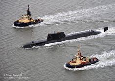 Escorted by tugs, Royal Navy submarine HMS Astute sails up the Clyde estuary into her home port of Faslane, Scotland for the first time following the journey from Barrow-in-Furness shipyard.
