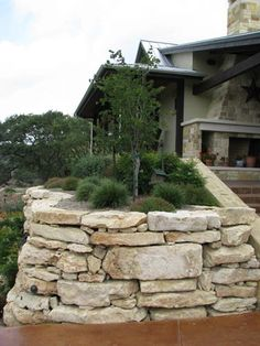 Limestone retaining wall in hill country style landscape. visit www.sagrows.com for more info.