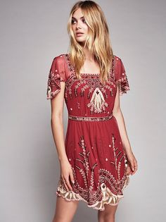 Notting Hill Mini Dress   Sheer mesh mini dress featuring allover embroidery and embellishment detailing with a scalloped trim. Short flutter sleeve with a squared neckline. Full slip with adjustable straps for a more customized fit.
