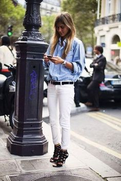 Women's' Light Blue Denim Shirt, White Skinny Jeans, Black Leather Heeled Sandals, Black Leather Belt, and Silver Watch