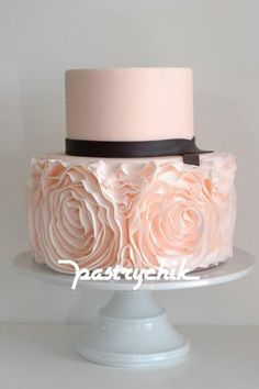 Feminine and romantic two-tiered pink wedding cakes with rosettes.