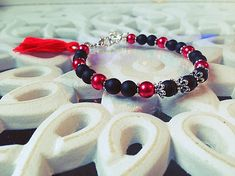 Bracelet femme fait main composé de perles en onyx mat, de perles en verres nacrées rouges, de perles en métaux (sans nickel) et dun pompon rouge. Le bracelet est ajustable grâce à sa chainette. Il mesure 18cm au plus court et 22cm au plus long. Envoyé avec un emballage pret à offrir. FRAIS, couleur très sympa