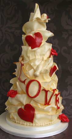 White Chocolate 'Love' Cake A tiered white chocolate wedding cake, covered entirely in white chocolate and decorated with hand moulded birds, hearts and roses.