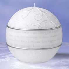 """Lillian Rose Fairy Tale Round Candle This unique round wedding candle measures 5"""" tall and 5"""" wide. Silver and pearl wax accents are used to decorate the candle, while a series of words line the candle's middle. Among those words are honor, fidelity, union, faith, commitment, happiness, love, blessed, cherish, devotion and heart. The round candle has a flat area at the bottom 2.75"""" wide so the candle can sit up. Price $21.90"""