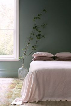 pale pink bedding with green walls and plant. / sfgirlbybay