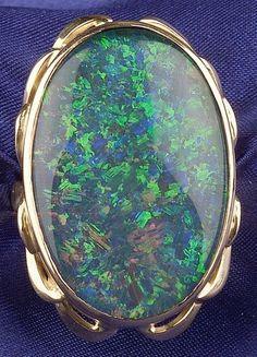 18kt Gold and Gem-set Ring, bezel-set with a black opal doublet, with stylized leaf motifs, size 7 3/4.  Estimate $500-700