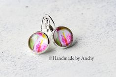 Silver colored dangle glass cabochon earrings with orchid by Anchy