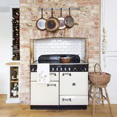 If you don't fancy a whole room full of rustic character, why not limit it to just one area of your kitchen? This range cooker has been fitted into an exposed brick chimney breast for a marvellously country-style centrepiece. Copper pans, a ceiling height wine rack, basketry and plaited garlic all press the style home