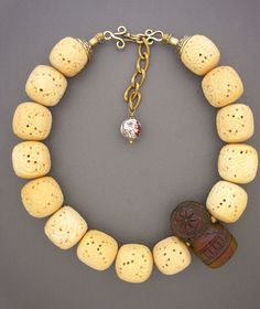 Necklace / A strand of carved beads (origin unknown) with an old carved resin Tibetan  chop /325