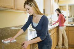 Two teenage sisters (16-18) cleaning kitchen counter - Andersen Ross/Digital Vision/Getty Images