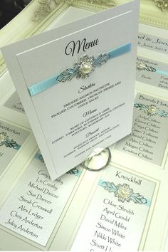 Framed Table Seating Plans by Michel Blott of Elegant Wedding Stationery | Luxury Table and Seating Plans Matching Breakfast Menus B Reception Stationery designed to fully co-ordinate with each table plan. Choice of adornments and ribbon colours available to match your own wedding theme SHOWN: IVORY SOFT SHEEN DOUBLE LAYERED CARD, AQUA BLUE RIBBON AND PEARL AND DIAMANTE ADORNMENT.