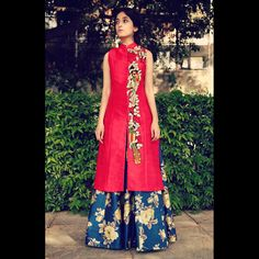 A Red long Achkan jacket with bird embroidered motifs on one side. The Achkan comes with a floral printed skirt.   Fabric composition: Silk  Lining: Shantone