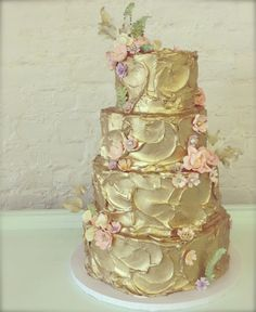 Stunning gold cake but would complement with striking deep red, purple or black instead of pastels