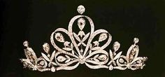 a belle epoque diamond tiara, featuring a large central motif of five doamond ribbon loops, each of which holds a pear-shaped diamond on a floral pinnacle