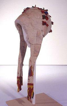 Inari, naisen AJOLAKKI - A driving/chasing headwear for women - Uudehkoa mallia. Pesä ommeltu neljästä kairasta, jotka ovat valkeaa vasantaljaa, saumoissa värikkäitä verasta tehtyjä koristehetaleita. Niskassa sisäpuolella pehmeästä valkeasta turkiksesta tehty reunus. Lakki on varustettu valkeasta vasantaljasta tehdyillä pitkillä korvuksilla, joiden keskikohdalla ja päissä on värikkäitä verasta tehtyjä koristehetalleita.