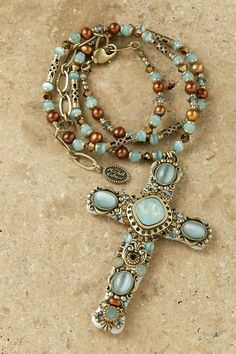 This artisan creates a necklace that is truly remarkable. She combines blue, and amber colored stones and Swarovski® crystals and puts them in settings of gold. To complete this elegant look, she also